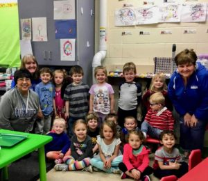 Group of kindergarten students smiling in front of newly installed radon mitigation pipe