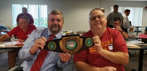 Two men holding a Radon Fighters champion belt