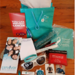 SWAG bag from a Cervivor conference showing brochures, sunglasses and more branded items