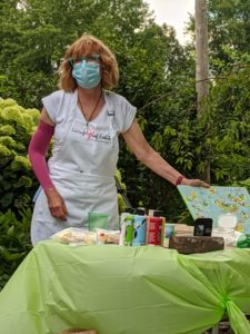 Woman wearing mask and a painter's apron hold a piece of art with a table containing paints and brushes is set in front of her.