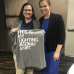 Two woman posing for a picture, one holding a gray t-shirt that says This is My Cancer Fighting Shirt.