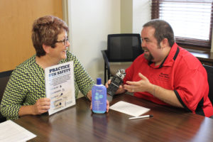 A woman (Becky Wolf) smiles and poses with a bottle of sunscreen and a sun safety tip sheet while she is interviewed by a DJ from Raccoon Valley Radio.